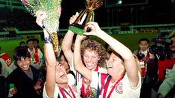 Julie Foudy, Michelle Akers-Stahl und Carin Jennings (v.l.) bejubeln den Sieg der USA bei den WM 1991 in China © picture-alliance/AFP