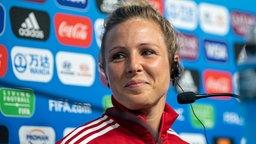 Fußball-Nationalspielerin Svenja Huth sitzt bei einer Pressekonferenz vor einem Mikrofon und lächelt.