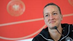 Die deutsche Frauenfußball-Nationaltorhüterin Almuth Schult bei einer Pressekonferenz auf einem Podium.