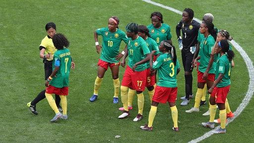 Mehrere Fußball-Nationalspielerinnen von Kamerun stehen zusammen mit einer Schiedsrichterin im Mittelkreises des Platzes beim WM-Spiel gegen England.