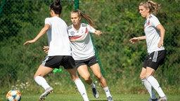 Die Nationalspielerinnen Sara Doorsoun, Klara Bühl und Verena Schweers (v.l.n.r.) während einer DFB-Trainingseinheit auf dem Fußballplatz.