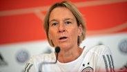 Die deutsche Fußball-Bundestrainerin Martina Voss-Tecklenburg sitzt bei einer Pressekonferenz auf dem Podium. © dpa picture alliance Foto: Sebastian Gollnow