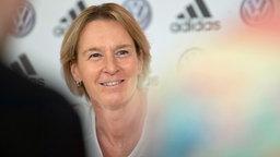 Die deutsche Fußball-Bundestrainerin Martina Voss-Tecklenburg sitzt bei einer Pressekonferenz auf dem Podium.