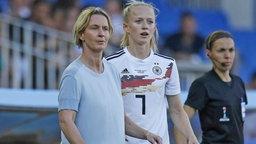 Bundestrainerin Martina Voss-Tecklenburg steht an der Seitenlinie neben Nationalspielerin Lea Schüller.