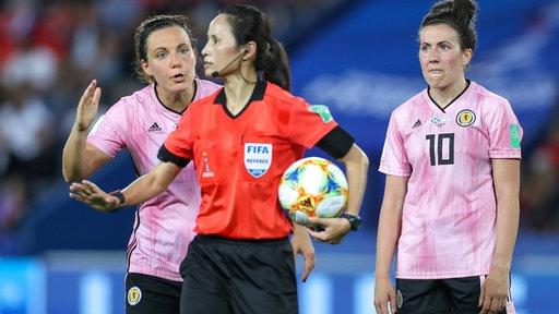 Schottische Spielerinnen diskutieren mit der Schiedsrichterin