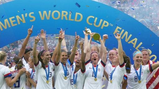 Megan Rapinoe hebt den WM-Pokal im Kreise ihres Teams in die Höhe.