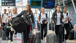 Die deutschen Fußball-Nationalspielerinnen Lena Goeßling, Klara Bühl, Johanna Elsig, Sara Doorsoun und Lena Oberdorf (v.l.n.r.) gehen an einem Bahnhof mit Taschen und Koffern in Richtung eines Zuges.